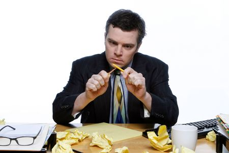 horsing around: Man in a business suit sitting at his desk frustrated and trying to snap a pencil. Surrounded by crumpled up pieces of paper. Isolated against a white background.