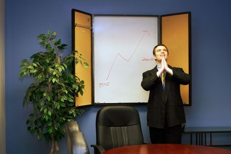 Businessman in a conference room with his hands joined praying for success Stock Photo