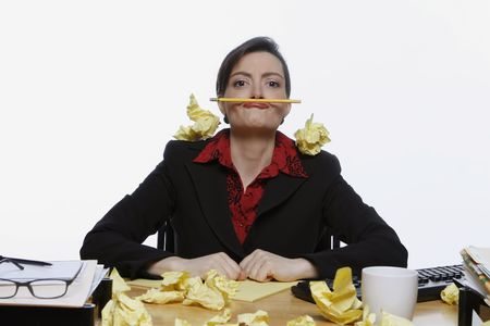 horsing around: Woman in a business suit balancing a pencil under her nose surrounded by crumpled up pieces of yellow paper. Isolated against a white background