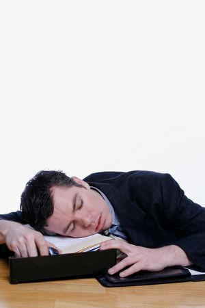 Businessman asleep at his desk. Isolated against a white background. photo