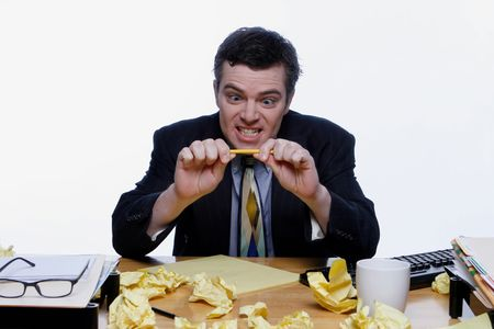 clowning: Man in a business suit sitting at his desk frustrated and trying to snap a pencil. Surrounded by crumpled up pieces of paper. Isolated against a white background.