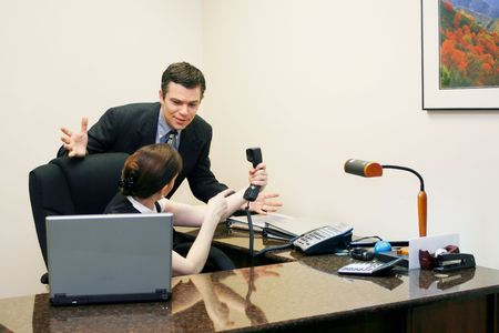 resignation: Male and female business colleagues arguing over who should take a phone call