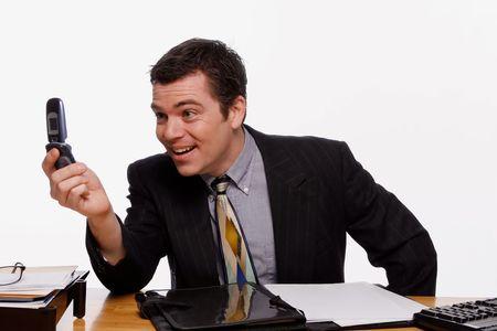 quizzical: Empresario busca en la pantalla de su m�vil con una torcida sonrisa en su rostro. Aislado contra un fondo blanco.