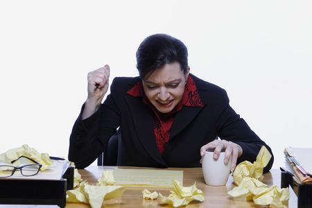 Woman in a business suit stabbing her pen in the air with frustration, surrounded by balls of crumpled yellow notepaper. Isolated against a white background. Stock Photo - 3002601