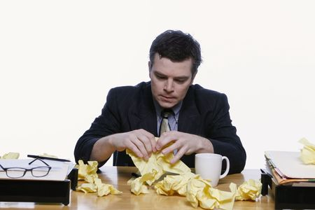 Businessman sitting at his desk looking dejected surrounded by scraps of yellow notepaper