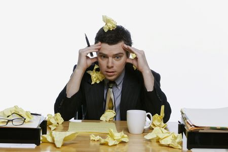 scrunched: Businessman sitting at his desk surrounded by and covered in balls of yellow notepaper. He has his hands on his head. Isolated against a white background. Stock Photo