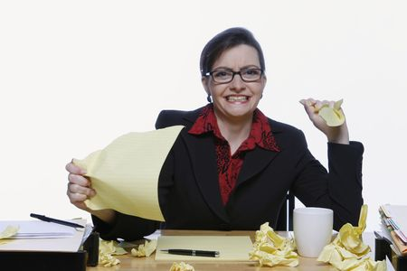 Businesswoman surrounded by crumpled up pieces of notepaper holding up a sheet and throwing a piece at the camera in disgust Stock Photo - 3002607