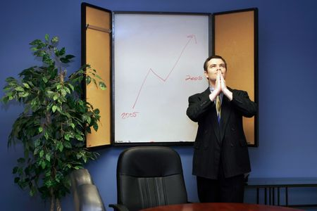 Businessman in a conference room with his hands joined praying for success photo