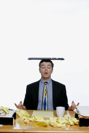 Man in a business suit meditating at his desk while balancing his keyboard on his head photo