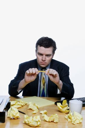 Man in a business suit sitting at his desk frustrated and trying to snap a pencil. Surrounded by crumpled up pieces of paper. Isolated against a white background.