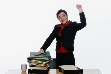 Businesswoman with her hand on a big pile of folders in her outbox pumping her fist in the air. Isolated against a white background. photo