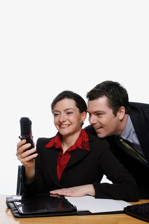 Businesswoman and businessman staring at her cell phone and smiling photo