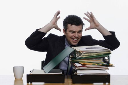 defiant: Businessman raising his hands to his head in frustration as he stares at a large pile of folders in his inbox. Isolated against a white background