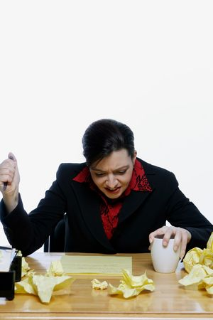 Woman in a business suit stabbing her pen in the air with frustration, surrounded by balls of crumpled yellow notepaper. Isolated against a white background. Stock Photo - 3002598