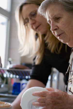 Adult woman and her elderly mother doing dishes at the kitchen sink together. Stock Photo