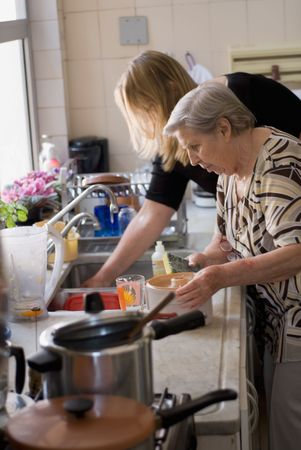 Adult woman and her elderly mother doing dishes at the kitchen sink together. photo