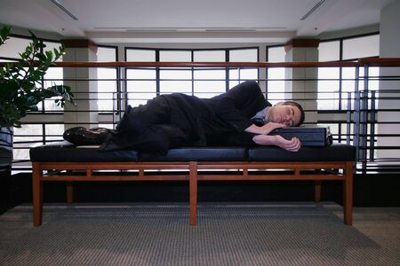 slacker: Man in a business suit asleep on a couch in an office hallway