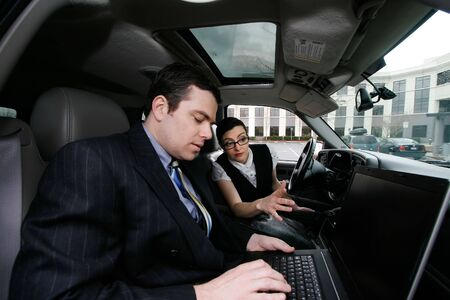 road warrior: A shot of a businessman and businesswoman sitting in a car looking at a laptop.