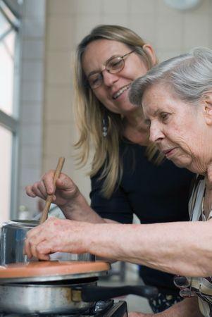 mere cuisine: Femme adulte et sa vieille m�re cuisine ensemble dans leur cuisine. L'ancienne dame est lev�e en place le couvercle d'un pot et dans la recherche.