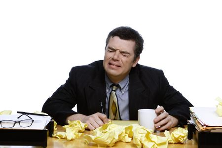 An isolated shot of a businessman sitting at a desk crying, while trying to write down ideas on yellow paper. Stock Photo - 3006747