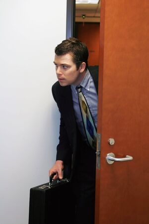 sneaking: A shot of businessman peaking his head out of a door to see if he can sneak out the office.