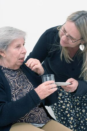 Adult woman helping her elderly mother with her medication. Isolated. Stock Photo