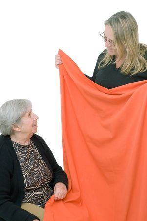 Adult woman and her elderly mother folding a bright orange piece of fabric. Isolated.