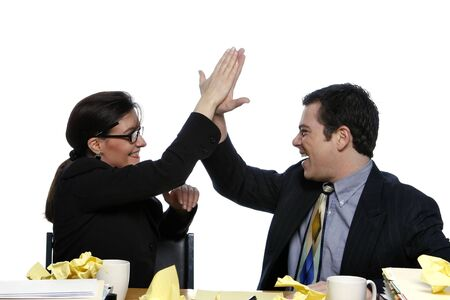 An isolated shot of a businessman and businesswoman giving each other a high five at a desk, littered with yellow paper. Stock Photo - 3006751