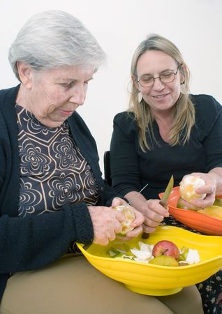 Adult woman and her older mother peeling fruit together. Isolated photo