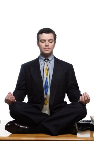 centering: An isolated on white shot of a businessman sitting on desk in a yoga pose.