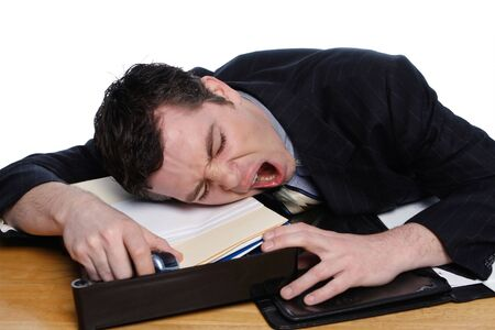 An isolated on white shot of a businessman resting his head on desk yawning. Stock Photo