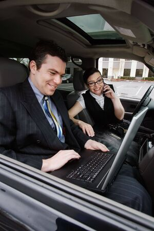 working: Male and female business colleagues working on a laptop while sitting in a car