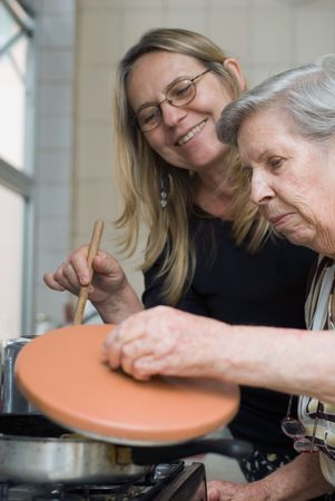 Adult woman and her elderly mother cooking together in their kitchen. The older lady is lifting up the lid of a pot and looking inside. photo