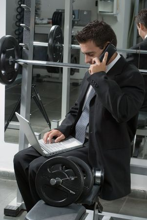 Man in a business suit sitting on a weight bench in a gym with his laptop and cell phone