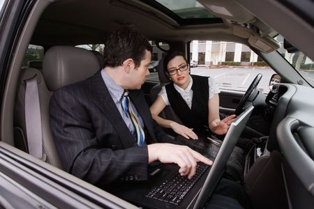 A shot of a businessman and businesswoman sitting in a car looking at a laptop. photo