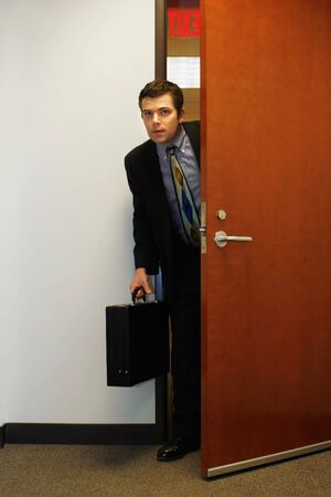sneaky: Caucasian businessman furtively peeking through a doorway