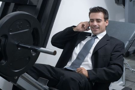 weight machine: A shot of a businessman, in a suit, sitting on a weight machine talking on a cellphone.