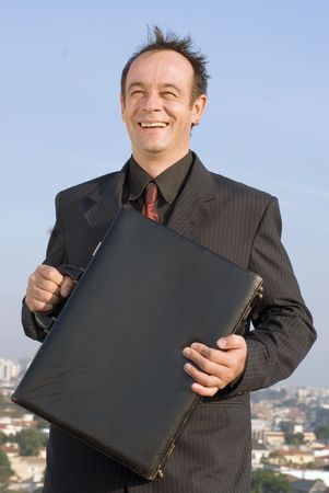 Businessman standing on a city rooftop and smiling while holding his briefcase close to his chest photo