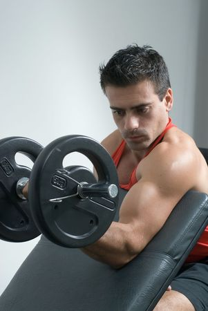 An isolated shot of male, athlete curling a dumbbell, with his left arm. Stock Photo