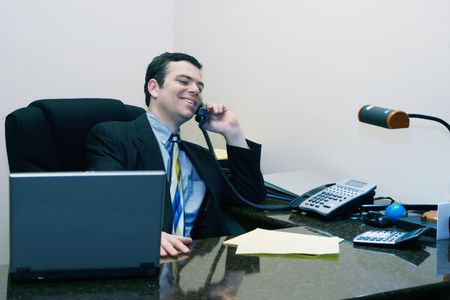 Man in a business suit smiling while he talks on the phone at his desk