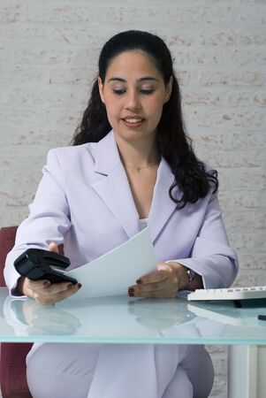 office stapler: An isolated shot of a businesswoman stapling papers. Stock Photo