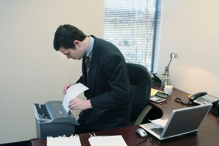 furtively: Caucasian businessman furtively shredding documents at his desk Stock Photo