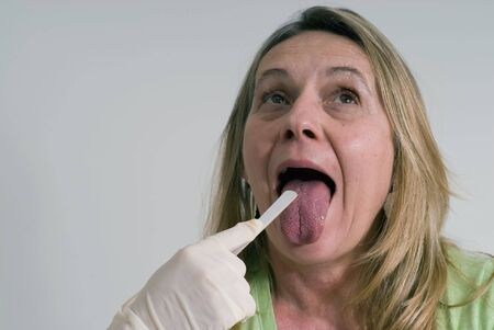depressor: An isolated head shot of a woman saying ah, as a nurse holds down her tongue with tongue depressor.