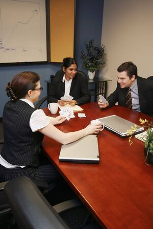 goofing: Group of business colleagues sitting in a conference room and playing cards instead of working Stock Photo