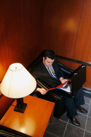 Businessman waiting in an office lobby with his briefcase open