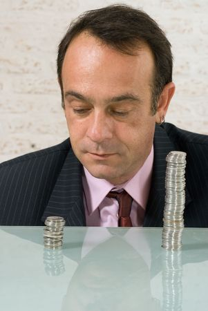 Businessman staring dejectedly at a shorter stack of coins to his right while a larger stack stands off to the right photo