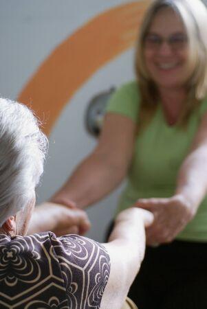 Una foto de un hijo adulto ayudar a su anciana madre se extiende a hacer. Foto de archivo - 3009966