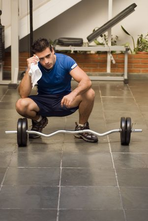 Man kneeling in front of a set of weights wiping himself off with a towel while taking a break Stock fotó