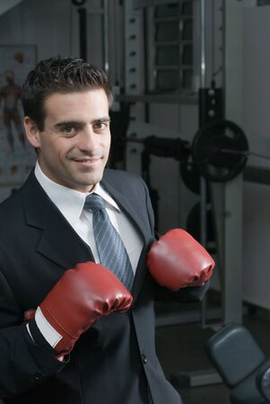 A shot of a businessman, in a suit, wearing a pair of boxing gloves. photo