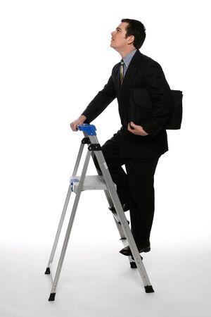 gaze: Zakenman met zijn aktetas clutched onder een arm beklimmen van een trap met zijn blik gericht op het plafond. Geïsoleerd tegen een witte achtergrond Stockfoto